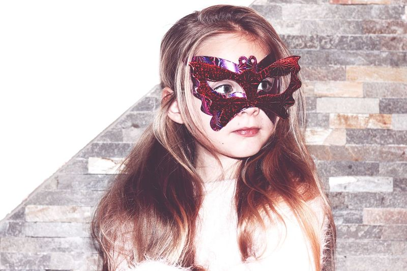Girl wearing masquerade mask against wall
