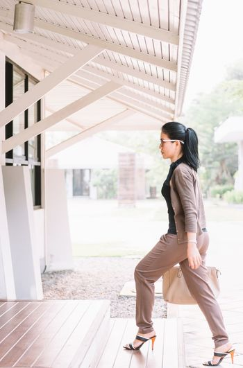 Side view of businesswoman walking on steps at office