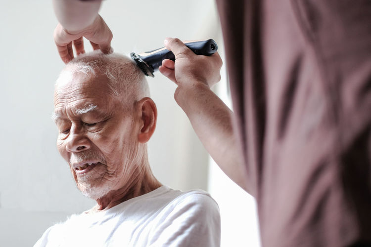 Midsection of barber cutting hair of customer