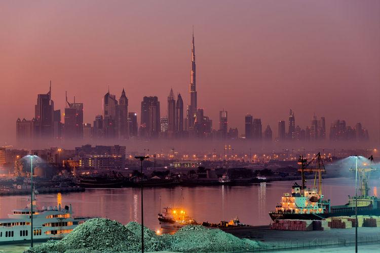 Illuminated buildings by sea at dusk