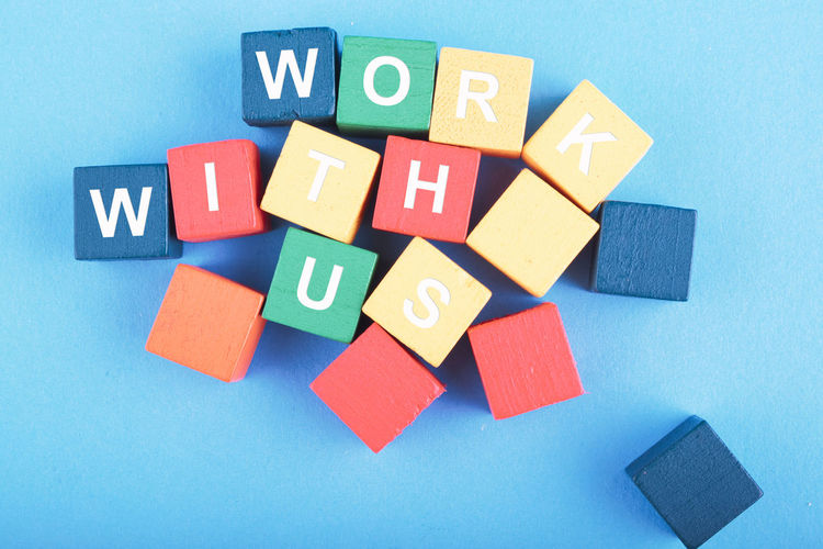WORK WITH US word on wooden cube over blue background Multi Colored Indoors  Blue Toy Toy Block No People Still Life Close-up Studio Shot Large Group Of Objects Directly Above Variation Choice High Angle View Communication Shape Group Of Objects Blue Background Creativity