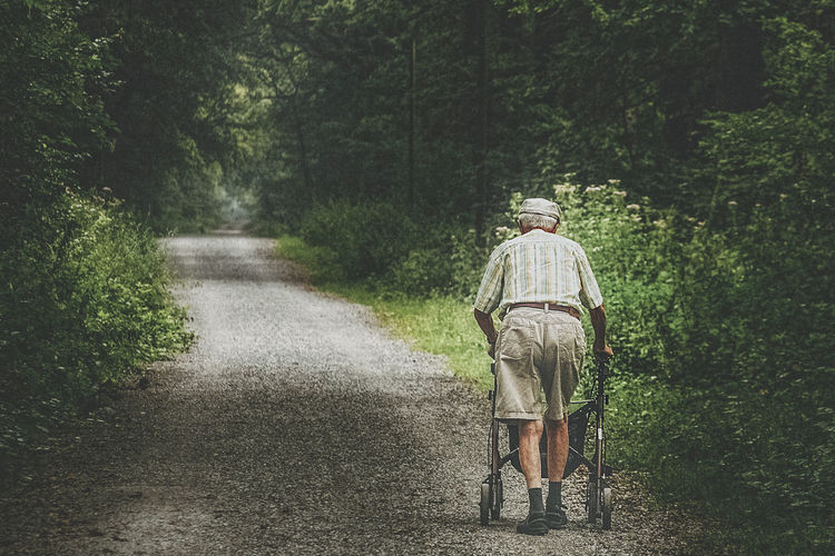 Rear View Full Length Of Senior Man With Mobility Walker On Road Amidst Trees