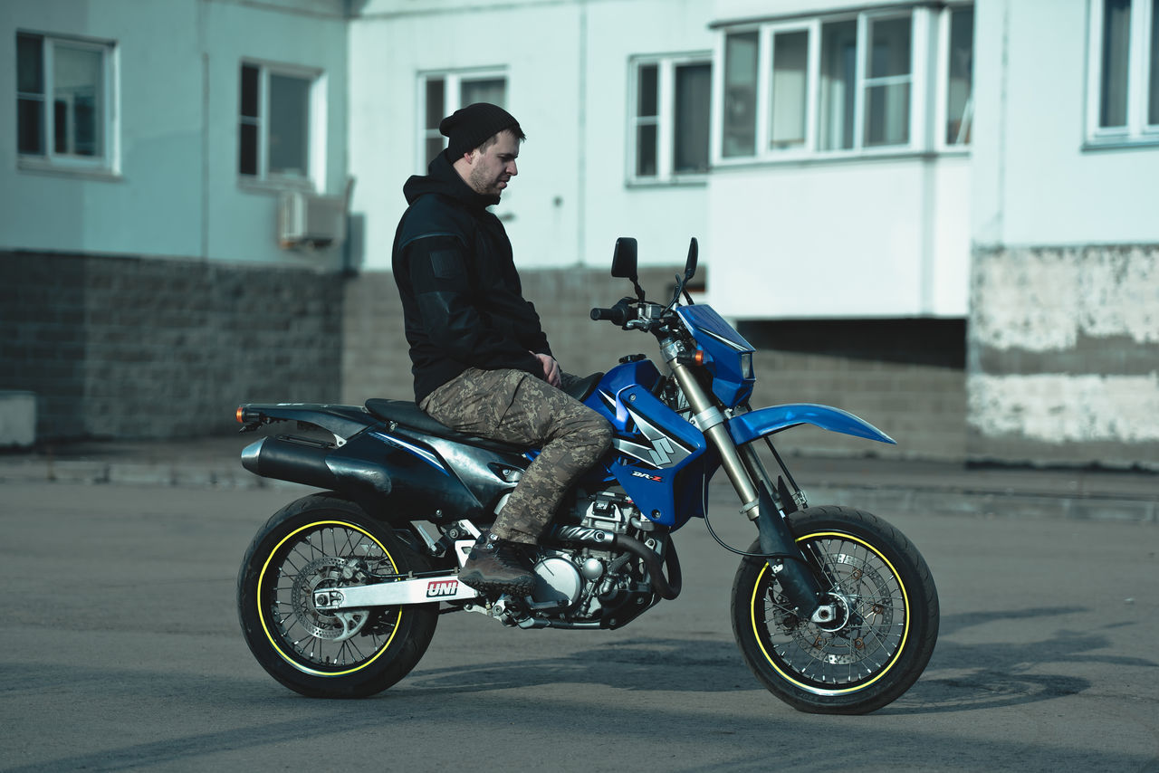 motorcycle, transportation, mode of transport, land vehicle, building exterior, riding, built structure, side view, architecture, stationary, real people, street, outdoors, day, helmet, crash helmet, one person, road, full length, biker, lifestyles, scooter, men, sports helmet, women, headwear, city, people