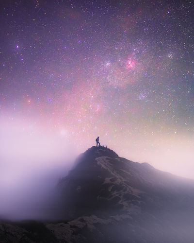 Silhouette person standing on mountain against sky at night