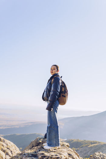 Man standing on mountain against clear sky