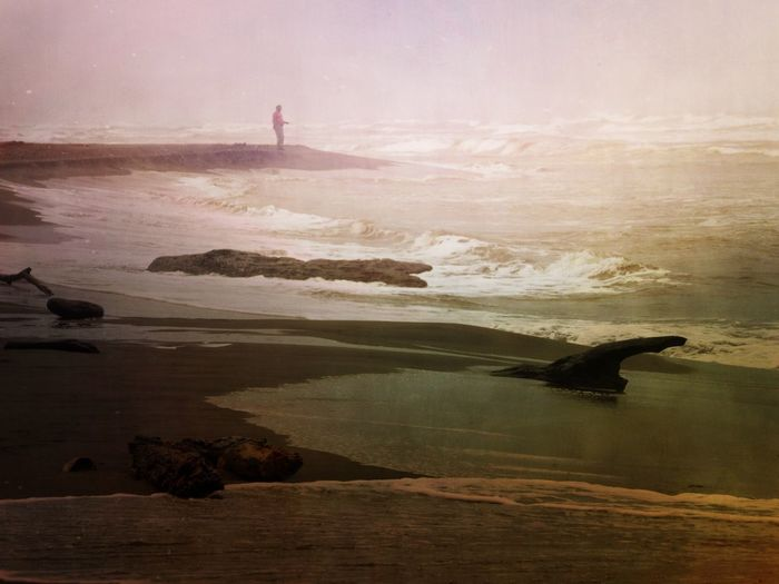 Mid distance view of man standing on rock formation in sea