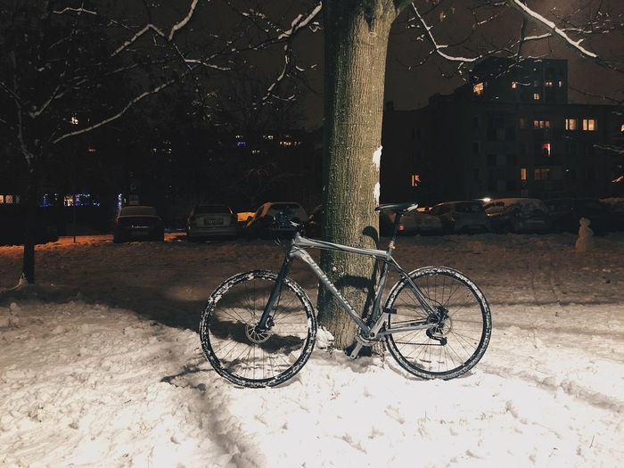Bicycle parked on street in city at night