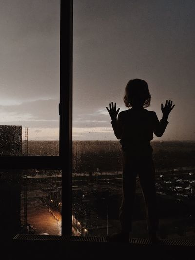 Rear view of silhouette boy standing by window against sky