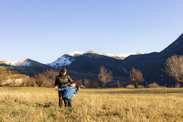 Mother and son standing on field against snowcapped mountains