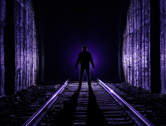 Rear view of silhouette man standing on railroad tracks at night