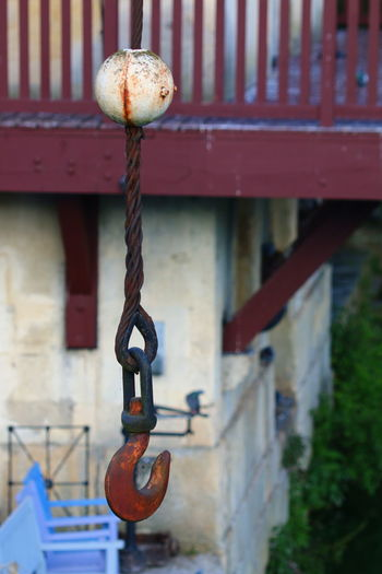 Close-up of chain hanging on railing against building