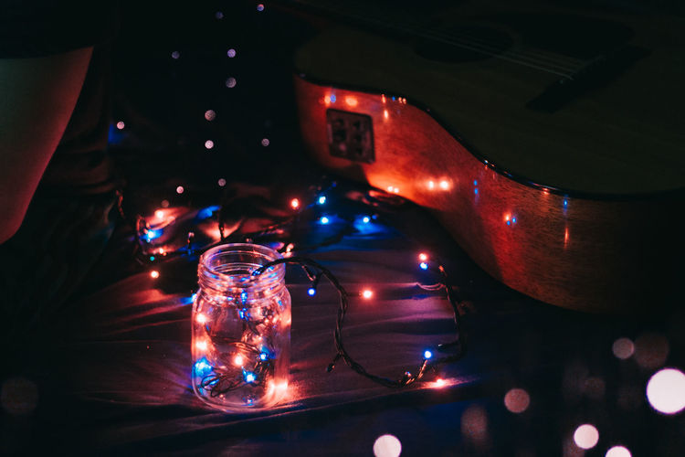 High angle view of illuminated string lights with jar and guitar on bed in darkroom
