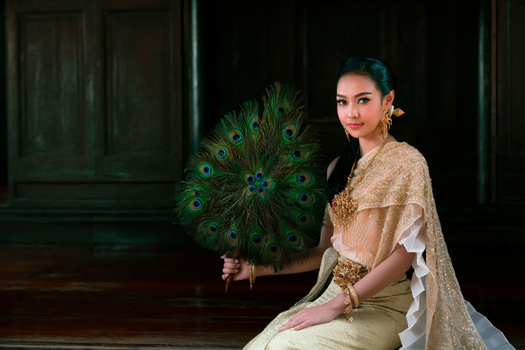 Portrait of young woman wearing traditional clothing and holding peacock feather