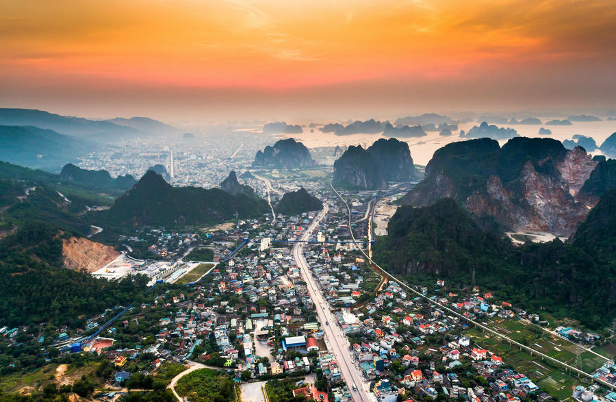 Bai Tu Long Bay City Cityscape Aerial View Architecture Beauty In Nature Building Exterior Car City Cityscape Cloud - Sky Day High Angle View Mountain Nature No People Outdoors Road Scenics Sky Sunrise Transportation Travel Destinations Tree