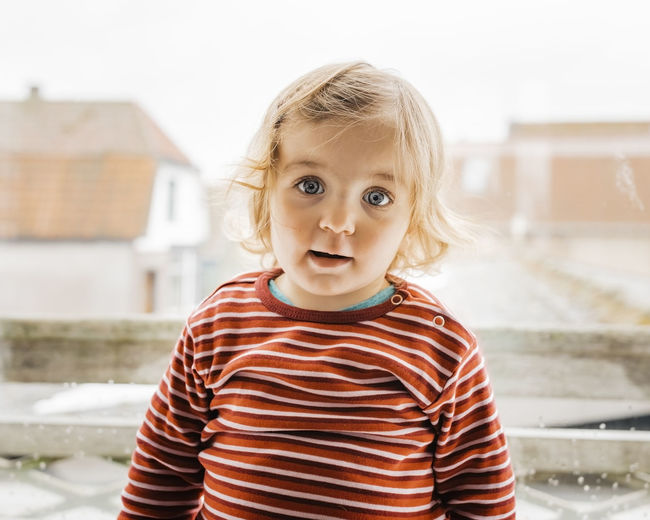 Portrait Of Cute Baby Girl Standing Against Window