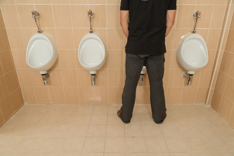 Low Section Of Man Urinating In Public Restroom