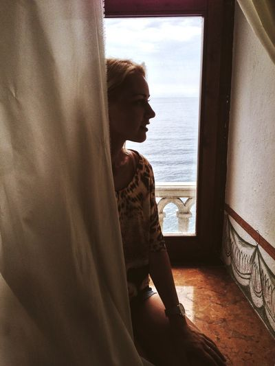 Young Woman Sitting Against Window In Cruise Ship