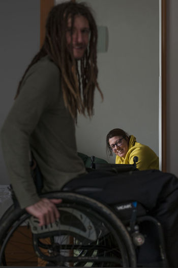 Man on wheelchair with smiling woman in background