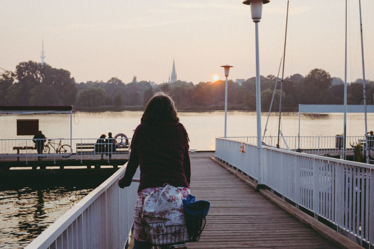 Rear view of woman standing on pier at river