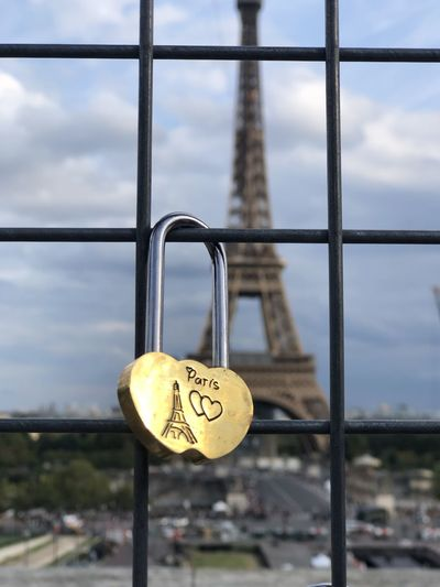 Close-up of padlocks on heart shape against sky