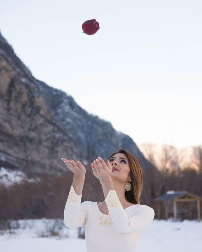 Young woman standing on snow against mountain