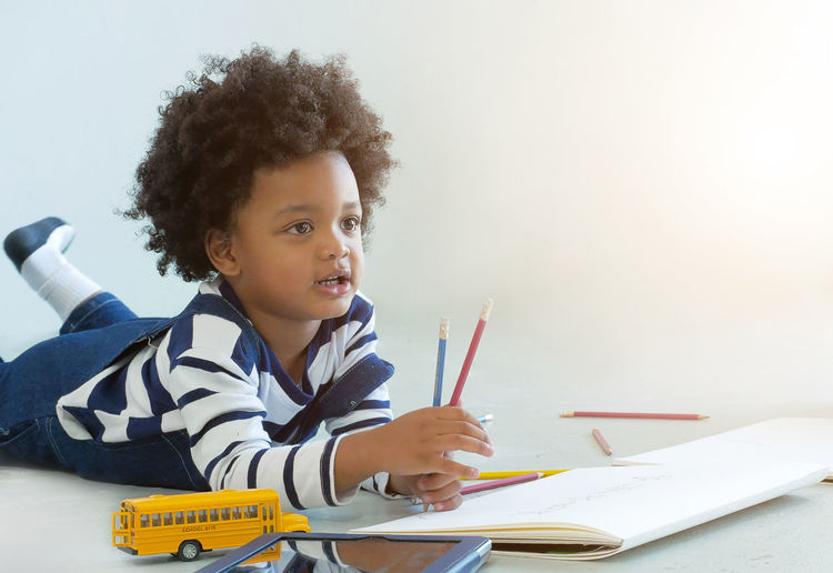 Boy with drawing book and toy lying on white background