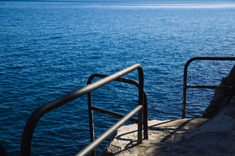 Railing by sea against sky