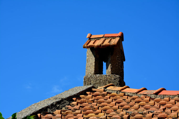 Low Angle View Of Old Roof Against Clear Blue Sky