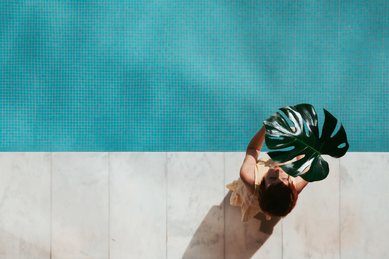 Directly above shot of woman holding leaf while sitting on poolside