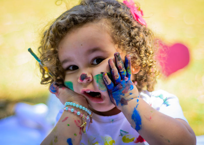 Portrait Of Cute Girl With Paint On Hand And Face