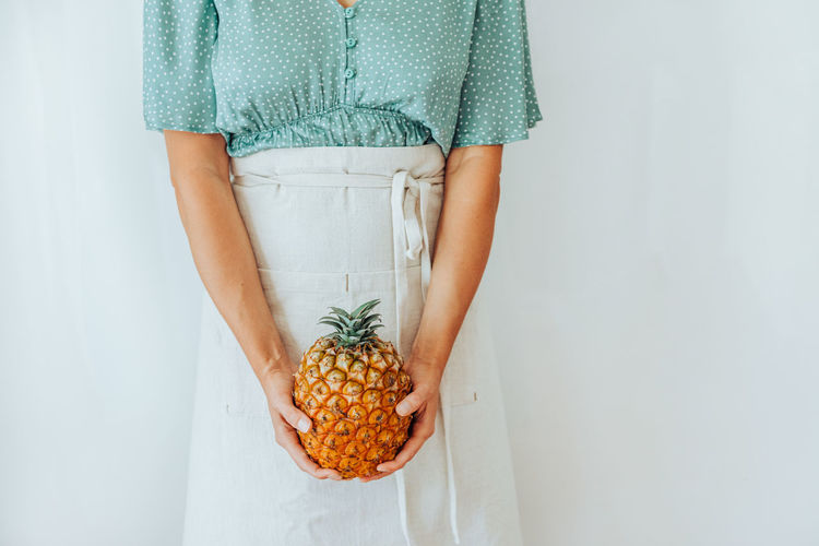 Midsection of woman holding fruit against white background