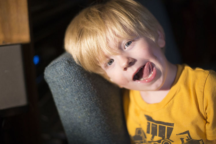 Portrait of boy sticking out tongue while leaning on sofa at home