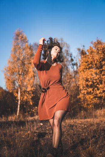 Woman with eyes closed dancing on field during autumn
