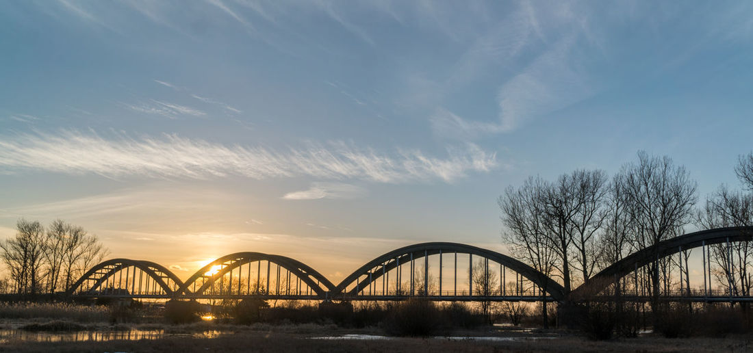 Metal arcs bridge over a river on sunset Architecture Bare Tree Beauty In Nature Bridge - Man Made Structure Built Structure Cloud - Sky Connection Day Nature No People Outdoors Sky Sunset Tree Water