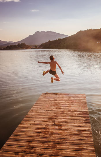 Rear view of boy jumping in lake during sunset
