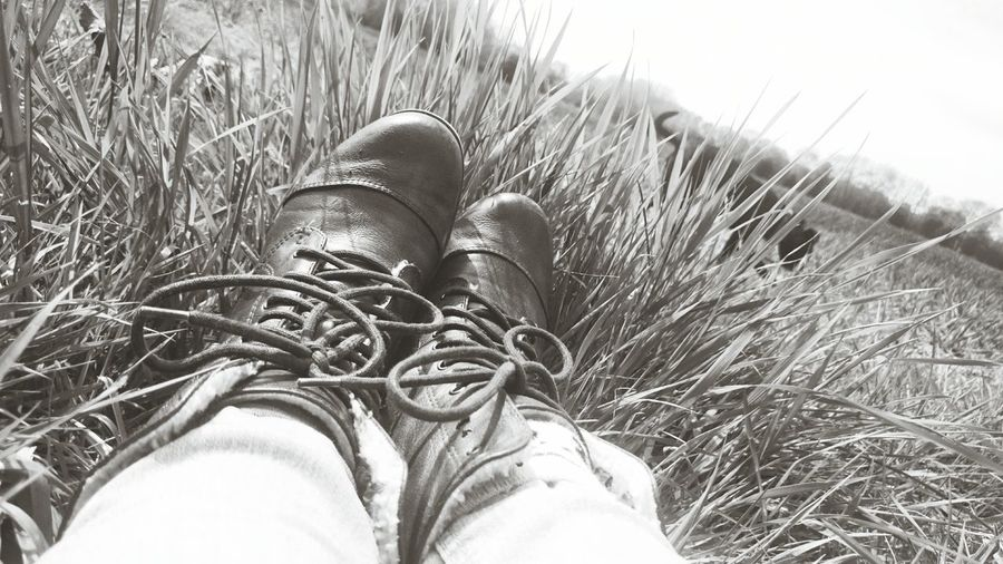 Low section of man wearing boots on grass