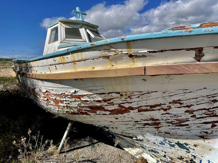 Abandoned boat moored on shore against sky