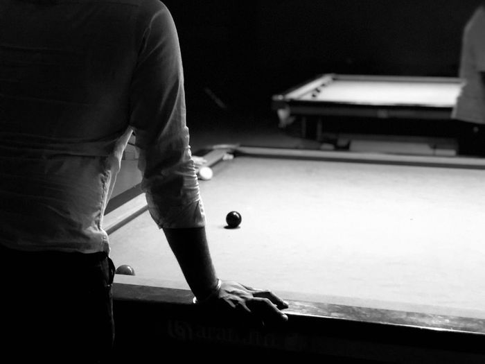 Midsection of man standing by pool table