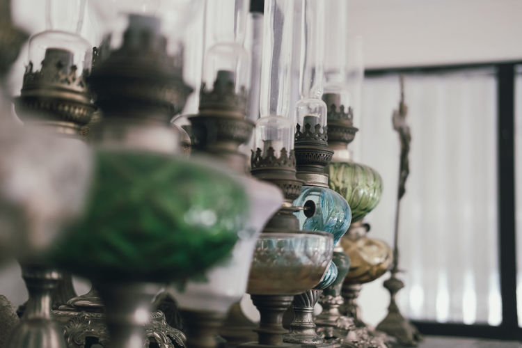 Close-up of antique oil lamps on table