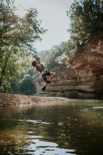 Mid-air Jumping Adventure Rock - Object Full Length One Person Lake Water Motion One Man Only Nature Men Shirtless Day Outdoors Adult People Only Men Tree Swimming