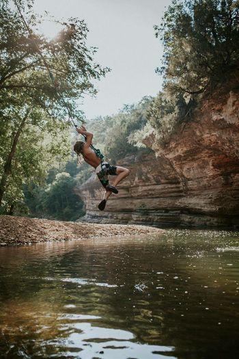 Man jumping on rock by lake