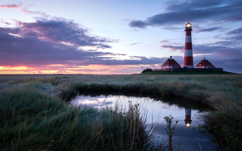 EyeEmNewHere Lighthouse Architecture Beauty In Nature Building Exterior Built Structure Cloud - Sky Day Grass Lake Landscape Lighthouse Nature No People Outdoors Reflection Scenics Sky Sunset Tranquil Scene Tranquility Travel Destinations Water Westerhever