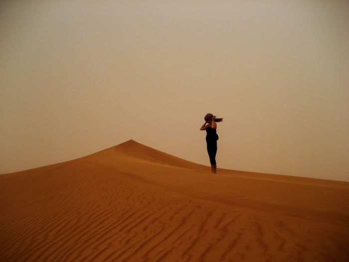 Woman standing on sandy desert against clear sky during sunset