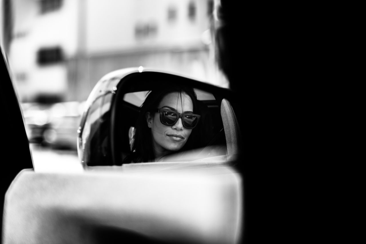 Reflection of woman wearing sunglasses in side-view mirror of car