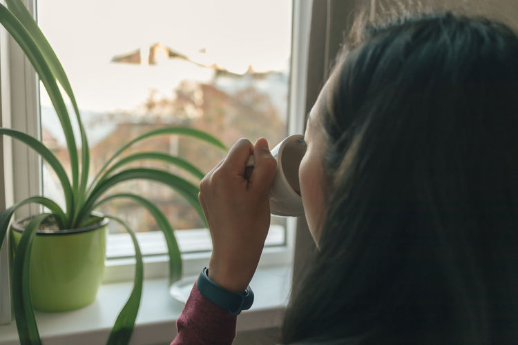 Close-up portrait of woman holding window at home