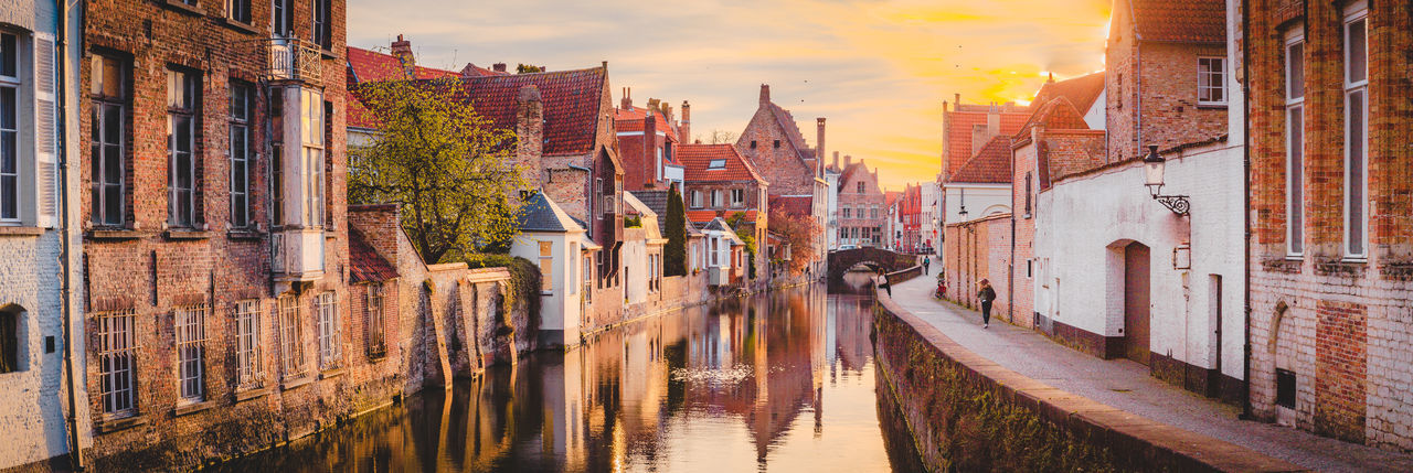 Panoramic view of canal amidst buildings in city during sunset