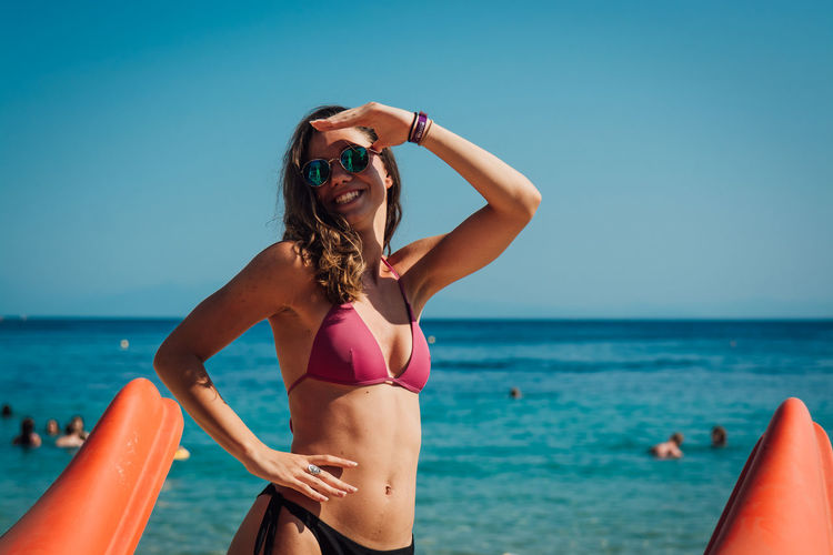 Young woman in bikini standing at beach against clear sky
