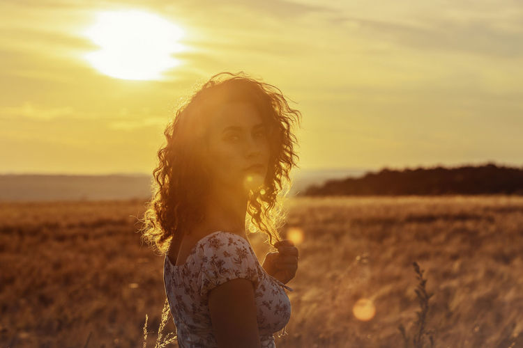 Portrait of woman standing on field against sky during sunset