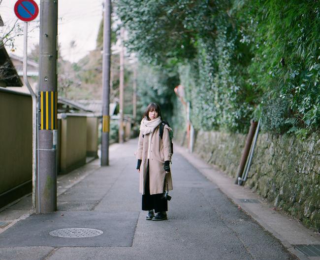 Woman walking on road along trees