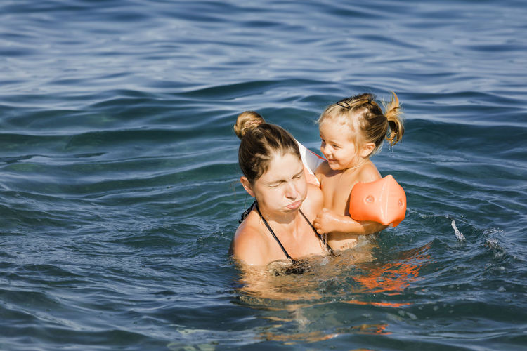 Woman and daughter swimming in sea